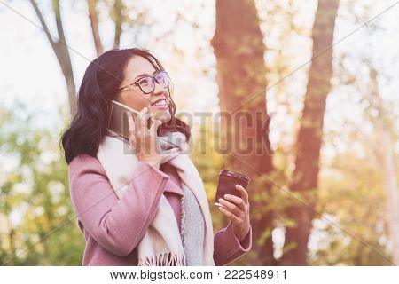 Beautiful young asian woman holding paper cup of hot drink and talking on the phone outdoor. Girl dressed in pink coat and white scarf.