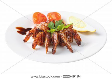 shrimps roasted in teriyaki sauce with  slice of lemon and cherry tomato on a white round dish isolated on white background. Side view.
