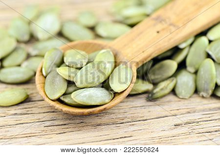 Pumpkin seed on wood background. Pumpkin seed is a rich source of zinc mineral.