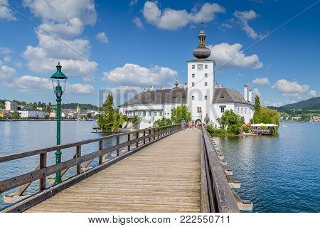 Beautiful view of famous Schloss Ort with wooden bridge at Lake Traunsee on a sunny day with blue sky and clouds in summer, Gmunden, Salzkammergut region, Austria