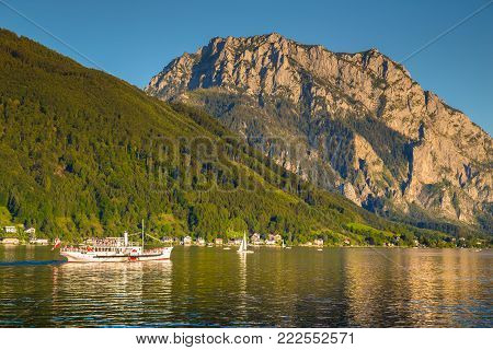 Beautiful view of traditional paddle steamer excursion ship on Lake Traunsee with famous Traunstein mountain in the background at sunset in summer, Gmunden, Salzkammergut, Austria