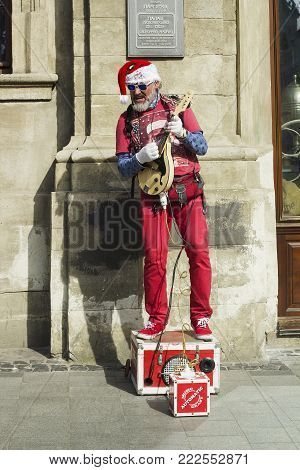 Lviv, Ukraine - 01.04.2017: Artist in Santa Claus red costume sings and plays electric guitar