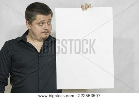 A man is holding an empty scoreboard or white square of paper. The eyes are directed at the white square. On a white background. copyspace