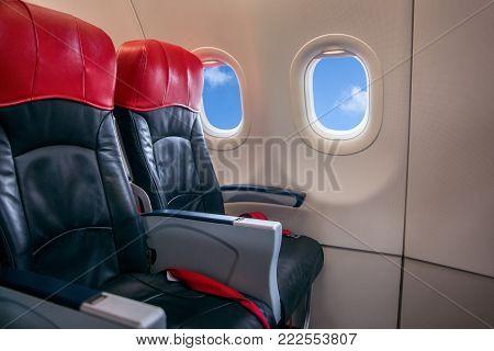 Passenger seats interior of salon. Empty aircraft seats and windows.