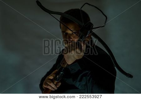 Arboleth in the hands of a young man. A man in dark camouflage glasses. Finger on the trigger. Looks at the target.