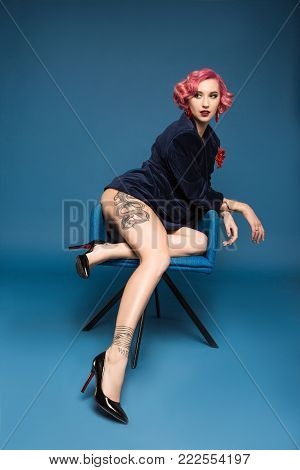 sexy tattoed pin up girl in jacket posing on armchair infront of blue background