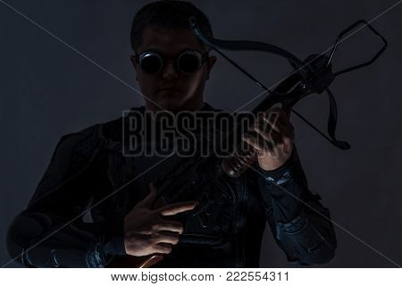 Arboleth in the hands of a young man. A man in dark camouflage glasses and a camouflage suit. Finger on the trigger. The man's gaze is directed forward.