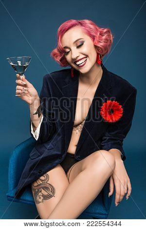 happy tattoed girl in jacket with boutonniere and wineglass infront of blue background