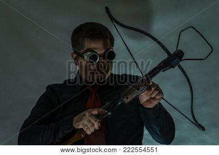 The arboleth in the hands of the young man is directed to the side. Dark camouflage glasses. A man's hand pulls a string of arbollet.