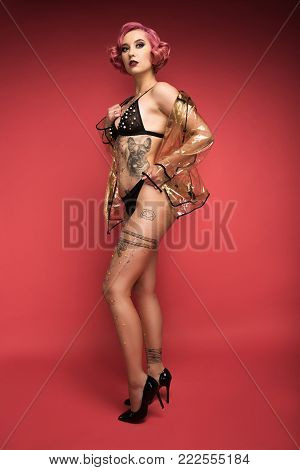 beautiful pin up girl with tattoos in lingerie and raincoat infront of red background