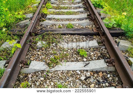 Old rusty railway. Between the concrete sleepers is one wooden sleeper. The only sleeper is not like other expresses individuality