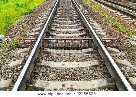 Old rusty railway. Between the concrete sleepers is one wooden sleeper with measuring sensors.