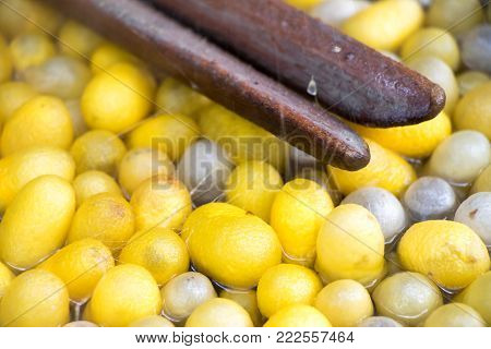 Closed up of vintage method for silk reeling and yellow and white cocoon on hot water background