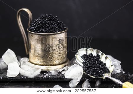 Black Caviar In A Silver Bowl With Ice And A Silver Spoon On Darck  Background. Silver Black Caviar