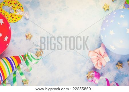 Bright colorful carnival or party scene of balloons, streamers and confetti on blue table. Flat lay style, birthday or carnival party greeting card with copy space, retro toned