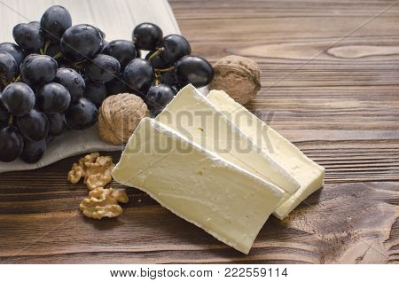 ie cheese with nuts and grape on wooden background