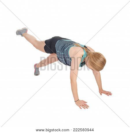 A lovely young woman doing exercises on the floor in shorts and seekers, isolated for white background