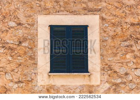 Old rustic stone house wall with closed window shutters, detail close-up, mediterranean background texture.wooden shutters