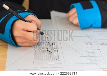 School Students hands taking exams, writing examination room with holding pencil on optical form of standardized test with answers and english paper sheet on desk doing final exam in classroom.