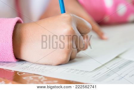 Students concentration holding pencils in hand doing multiple-choice quizzes testing exams answer sheets exercises in school, Tests is concept assessment intended to measure knowledge skill aptitude