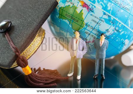Graduation cap with Miniature figurine Businessman standing near globe earth International study day. Student hat and world graduating cap student. Globe abroad Education in sucess symbol.