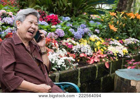Elder Woman Talk On Mobile Phone In Garden. Elderly Female Speaking On Smartphone In Park. Senior Ha