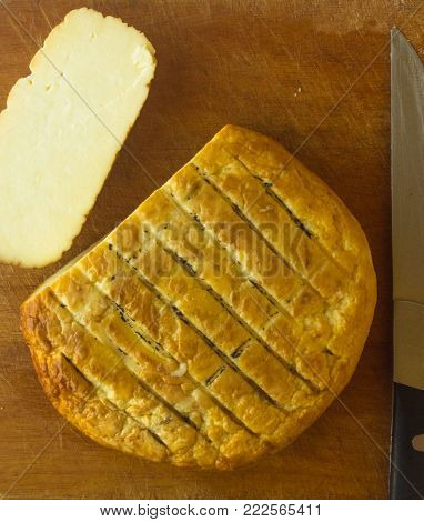 cut head of traditional Adygei cheese handmade with knife on wooden Board