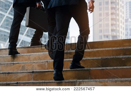 group of young handsome business man holding briefcase and walking up stairs going to work time at morning in the city, determination, confidence, lifestyle, rush hour, grow up and successful concept
