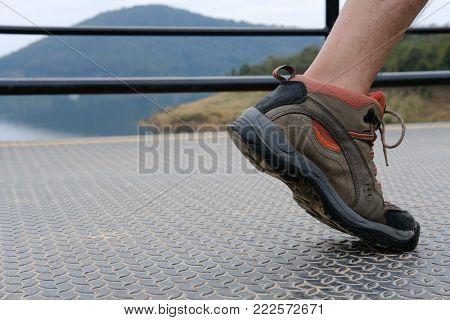 Feet Of Traveler Man Walking On Footbridge. Tourist Crossing Through Bridge. Travel Lifestyle, Summe