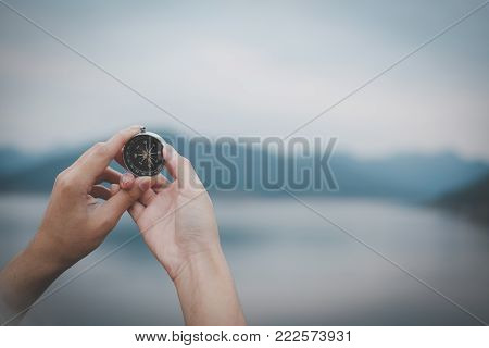 Hand Holding Compass For Searching Direction Outdoor. Man Seeking Way With Nature Background. Travel