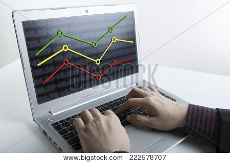 human hands of a person working on a computer with graphs