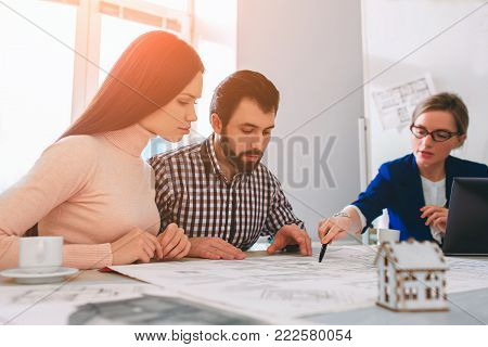 Young family couple purchase rent property real estate . Agent giving consultation to man and woman. Signing contract for buying house or flat or apartments. Discussion of size