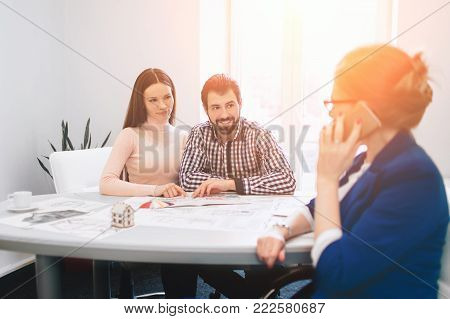 Confident Broker With Home Sellers Behind. Young family couple purchase rent property real estate . Agent giving consultation to man and woman. Signing contract for buying house or flat or apartments.