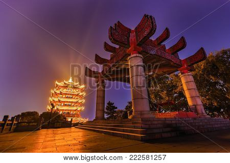 WUHAN, CHINA - 27 OCTOBER 2017 - Wide angle HDR (high dynamic range) shot of bell tower against the illuminated Yellow Crane Tower at night on Sheshan (Snake Hill) in Wuhan, Hubei, China