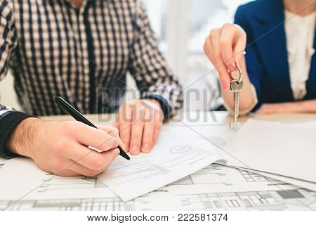 Young family couple purchase rent property real estate . Agent giving consultation to man and woman. Signing contract for buying house or flat. Sign a contract or agreement. Business Documentation.