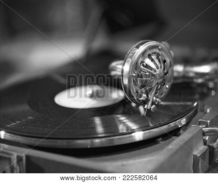 Retro styled image of a collection of old vinyl record lp's with sleeves. Browsing through vinyl records collection. Music background. Copy space. Old vintage gramophone in black and white.