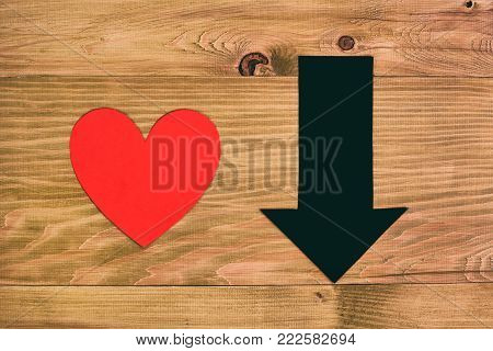 Image of heart shape and arrow going down on wooden table,relationship difficulties concept