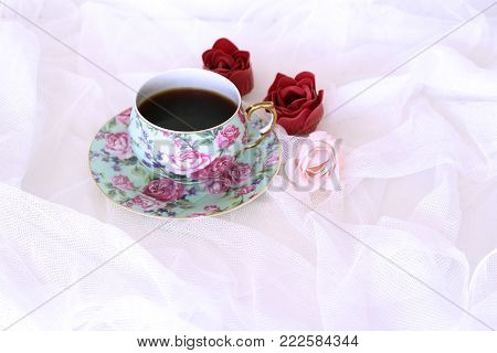 Morning hot coffe in mug and little red and pink flowers on white satin background. Closeup, top view. Seasonal, morning coffee, Sunday relax and still life concept, free place for text