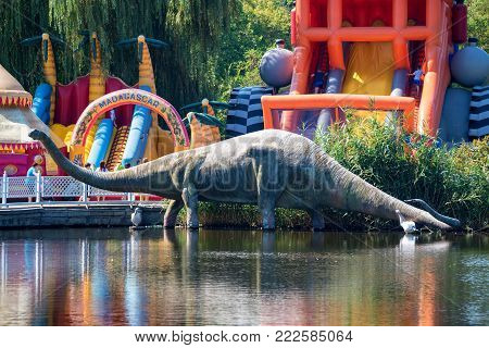 ROSTOV-ON-DON, RUSSIA - CIRCA AUGUST 2017: Statue of dinosaur on lake in Rostov zoo with inflatable bouncers in background. Taking up 100 hectares of land this Zoo is one of the biggest zoos in Russia