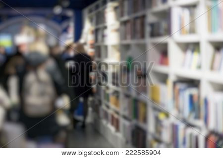 Unrecognizable people, bookshelves with books, manuals and textbooks on bookshelves in bookstore, for blurred backdrop. Concept interesting places to visit, read, information and learning