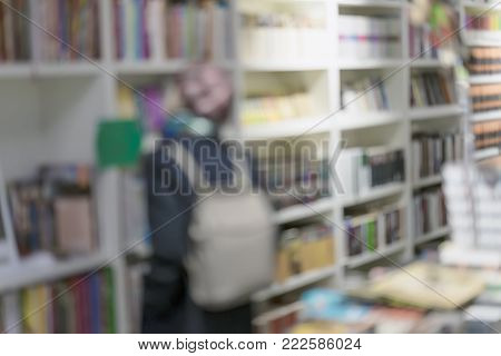 Girl and blurred bookshelves with books, manuals and textbooks on bookshelves in library or in bookstore, for backdrop. Concept of reading, education