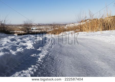 Snowy road and dry grass. Winter background. Snowy background. Winter landscape. Snow background. White snow. Snow style. Snowy road.