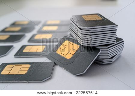 gray SIM card for phones collected in a column, next are cards, lots of cards