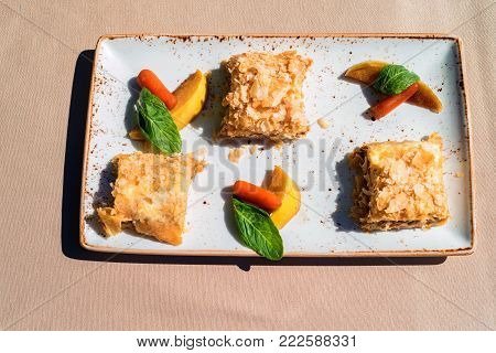 Top view of delicious dessert in restaurant made of three pieces of puff cake and fruit