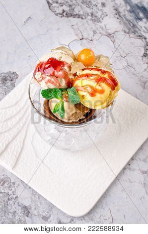 Top view close up. Three balls of multi flavor ice cream with Scoops of Chocolate, Vanilla and Fruit Ice Cream with Fresh Mint in Glass Dish on a white plate on a gray background. Restaurant kitchen, Eating concept