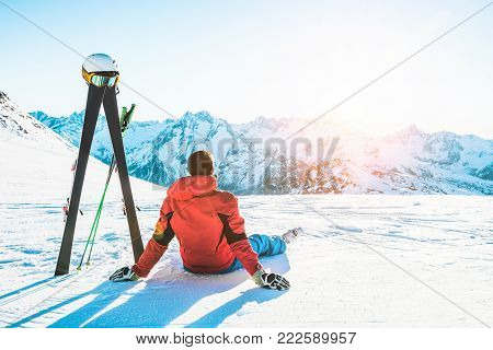 Skier athlete sitting in alpes mountains on sunny day - Adult man enjoying the sunset with skies gear next to him - Training and vacation concept - Focus on male body
