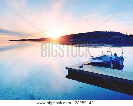 Motorboat for sport fishing tied to a wooden floating dock. Fishing boat with fishing rods in hangers  in bay port, sunset calm water.