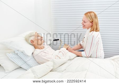 Woman makes a medical visit to bedridden senior citizen in the hospital