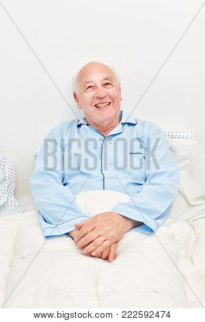 Senior man lies ill in bed in retirement home and smiles contentedly
