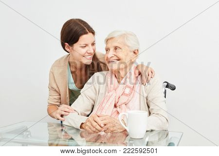 Caring care woman hugging a happy elderly woman on home visit
